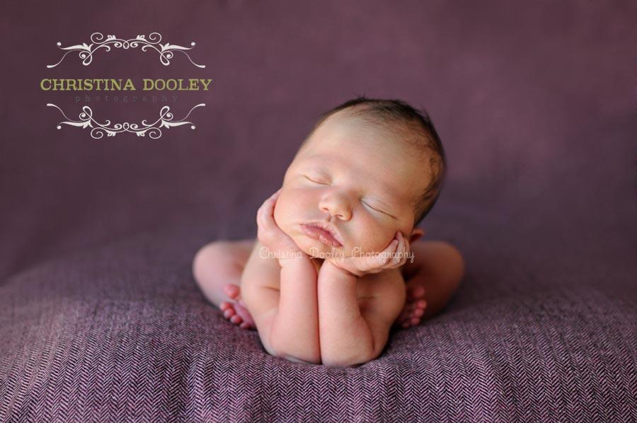Newborn holding head in hands