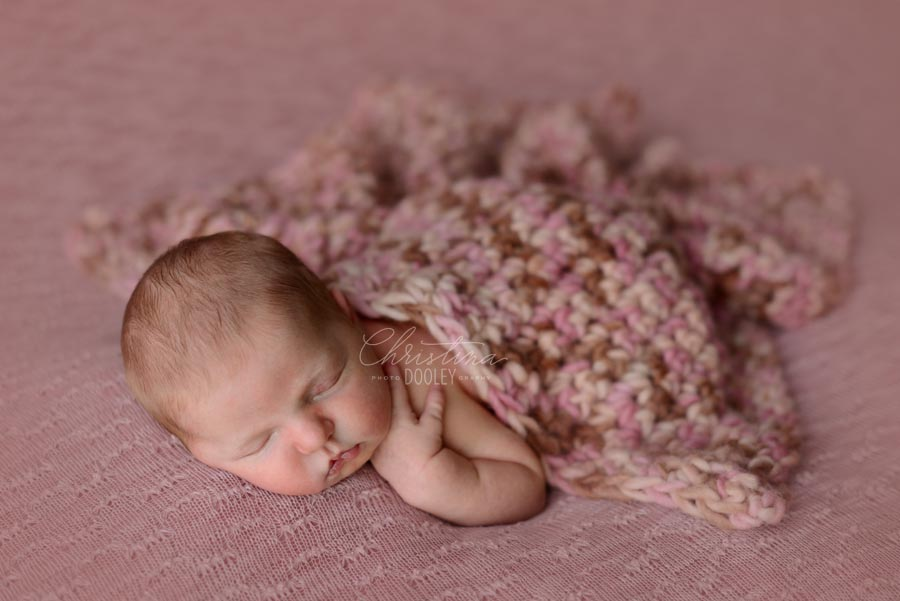 Newborn baby girl sleeping on pink with a knit pink blanket from JD Vintage Props