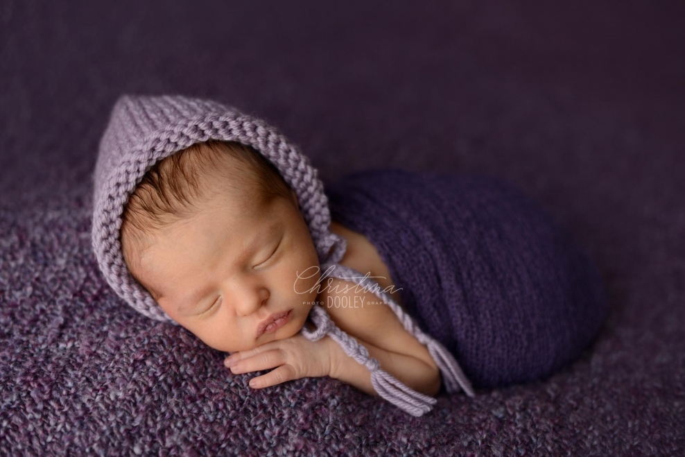 Baby girl wrapped in purple with a purple knit hat from goodnight mouse.