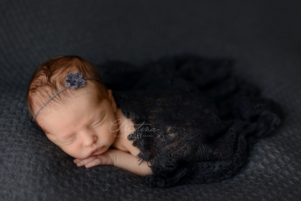 Newborn girl on gray with with gray wrap and headband from prop cartel