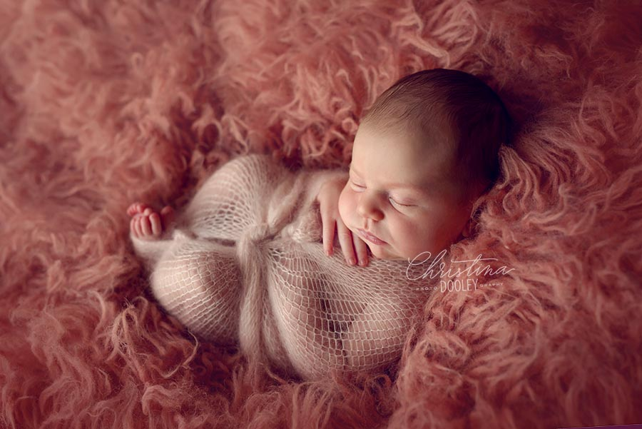 Newborn girl wrapped in pink knit wrap and posed on a blush pink float from Simply Pure Flokati, Nicole Smith Photography.