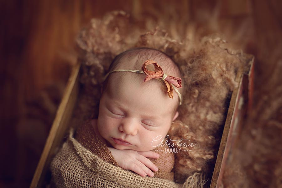 Newborn baby girl sleeping in box on top of brown fur wearing a rust colored bow headband from Ivy and Nell.