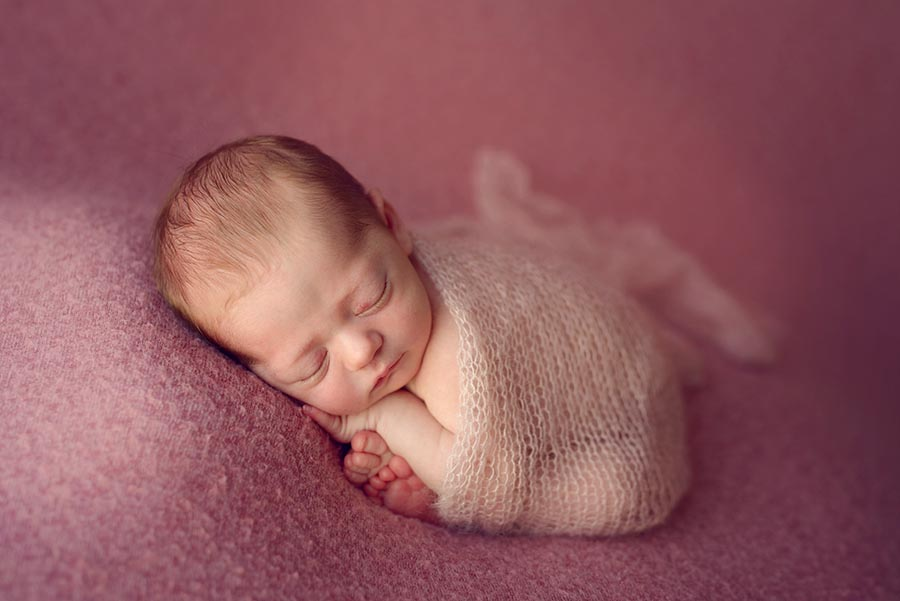 Baby girl sleeping on pick wrapped in knit blanket made from Goodnight Mouse Props