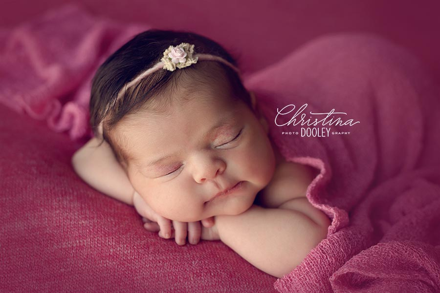 Newborn photo session of baby girl with a ton of hair and smiling