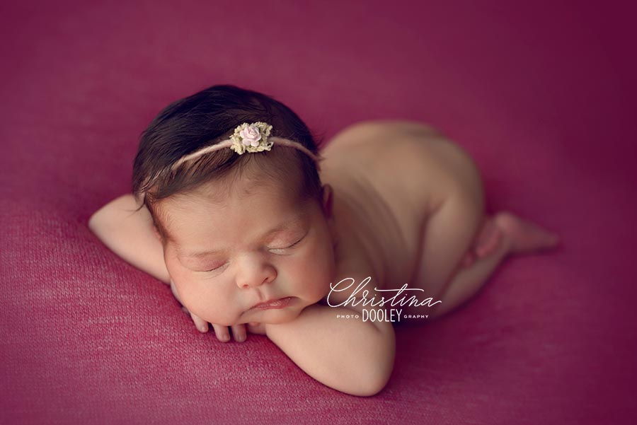 Baby girl photographed on pink in Denver Colorado.