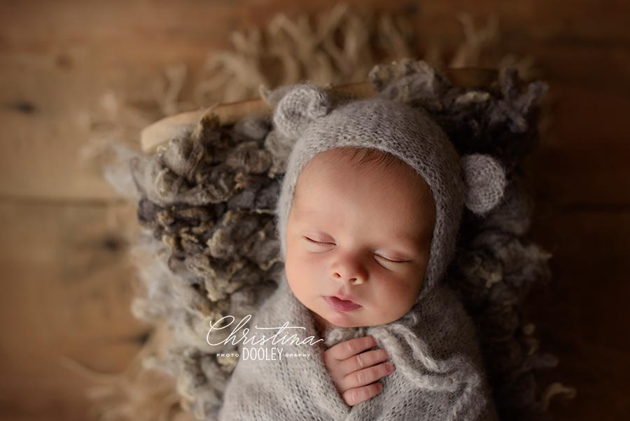 Newborn wrapped in and place in a baby bed wearing the cutest bear hat by Moknmba baby Props and more.