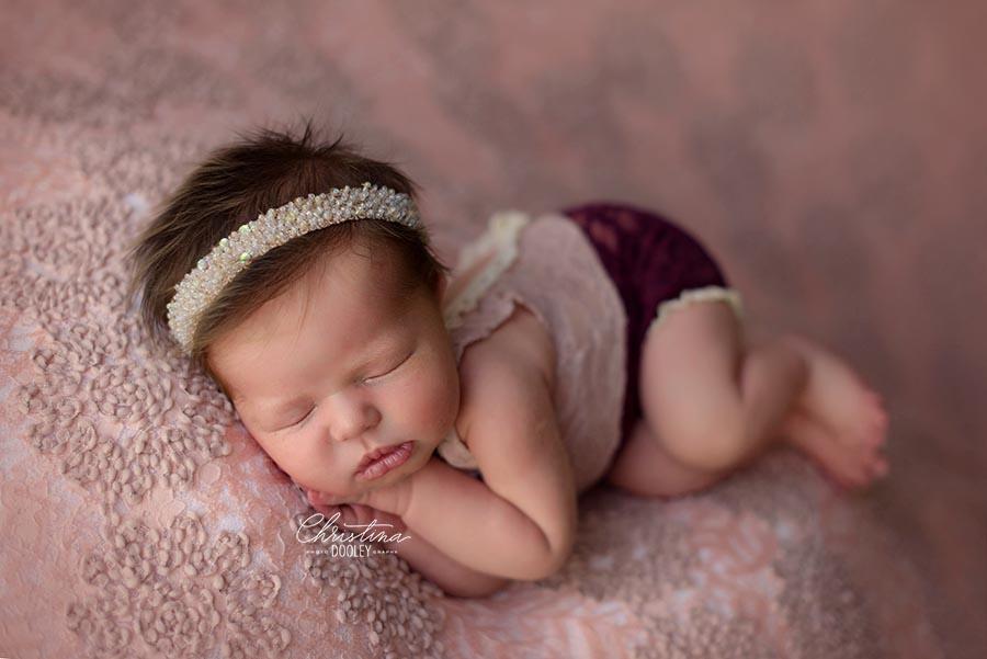 Newborn girl wearing a sparkly tie back and a delicate romper from Adorable Props for her newborn photos in Denver, Colorado.