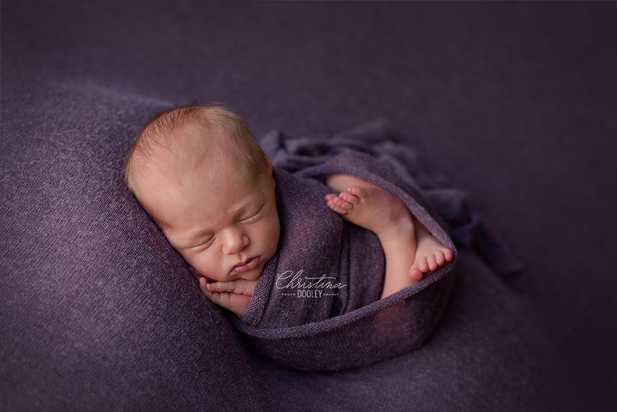 Newborn girl posed in the womb pose on purple with feet on chest and hands under her chin
