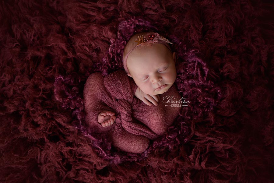 Newborn Girl photographed swaddled in a wine colored wrap and tie back made from Ivy and Nell on a wine closed Luneberry Flokati