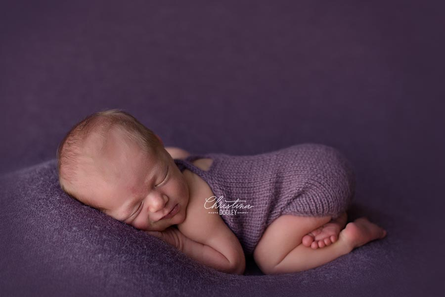 Newborn photo session, baby is posed in tushie up pose on purple wearing a romper from Zoe and Oliver.