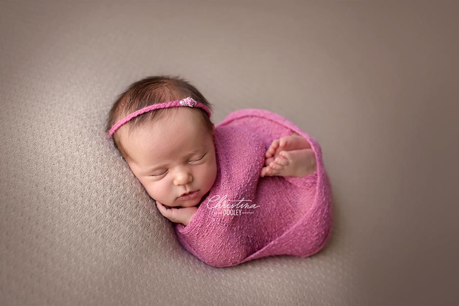 Baby swaddled in pink posed in the womb pose on a neutral lace background from AR Backdrops