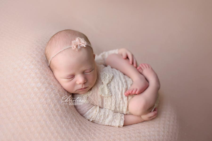 Newborn in Womb pose wearing a ruffled cream onesie from Adorable Props