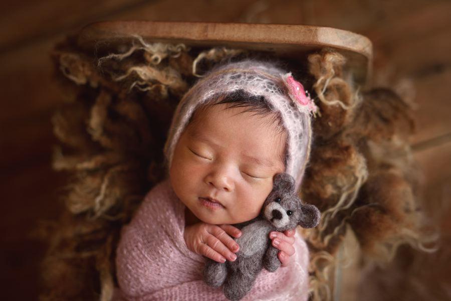 Close up of newborn girl wearing a pink bonnet holding a bear stuffy