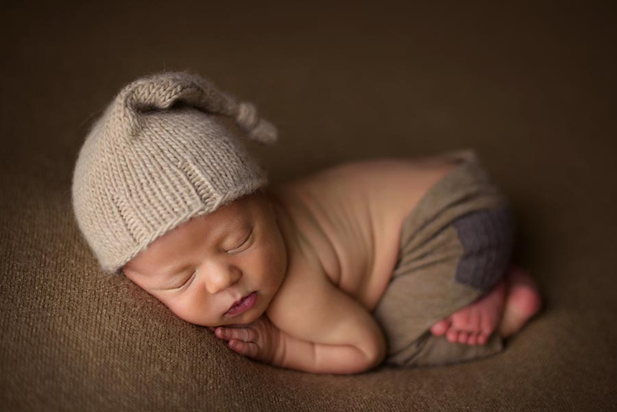 Sweetest baby boy photographed on brown with brown pants and sleep hat.