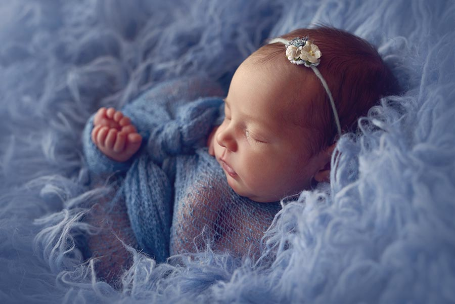 Newborn baby girl wrapped in blue for her photos.