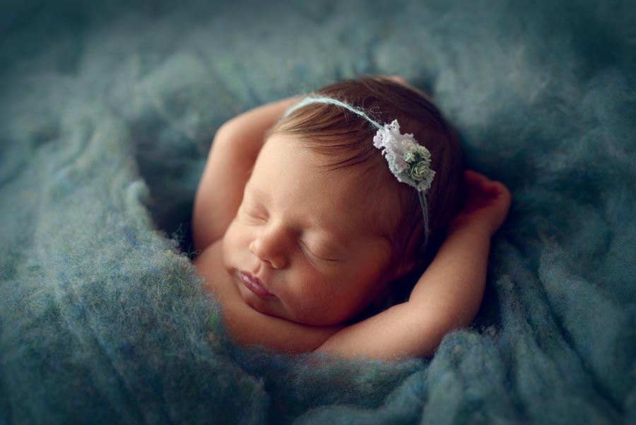 Baby girl in monkey pose for newborn photos wearing a teal tie back from Princess and Pea Prop Shop