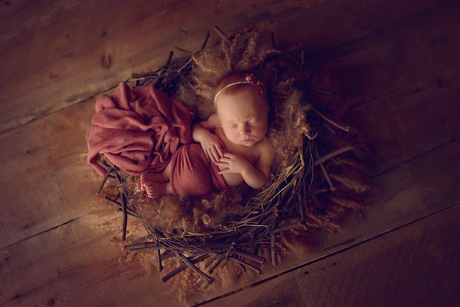 Newborn Baby Girl photo in Denver, sleeping on soft curly fur in a nest