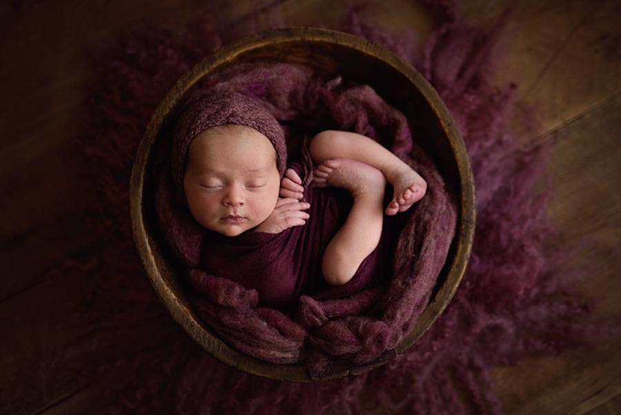 Baby snuggled in bowl in mauve bonnet and fluff from Oh so fleeting bowl from JD Vintage Props.