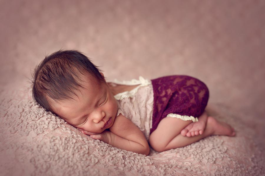Baby girl in Berry Colored Lace outfit sleeping on pink floral background for her newborn session.