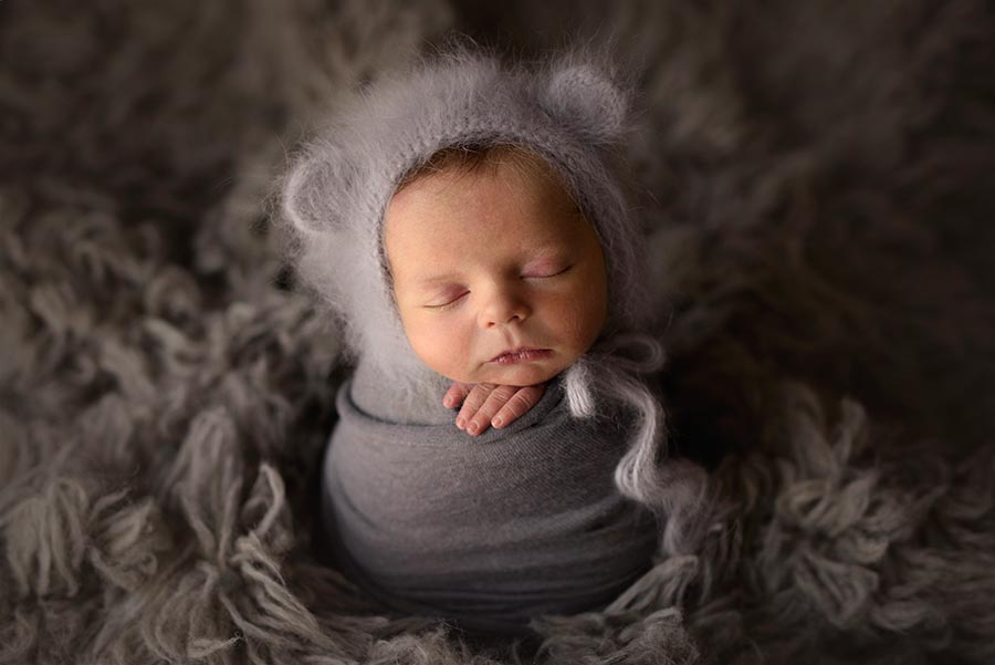 Baby boy wearing an angora knit bear hat from Lee Crochet wrapped in gray for potato pose on a gray flokati from JD Vintage Props