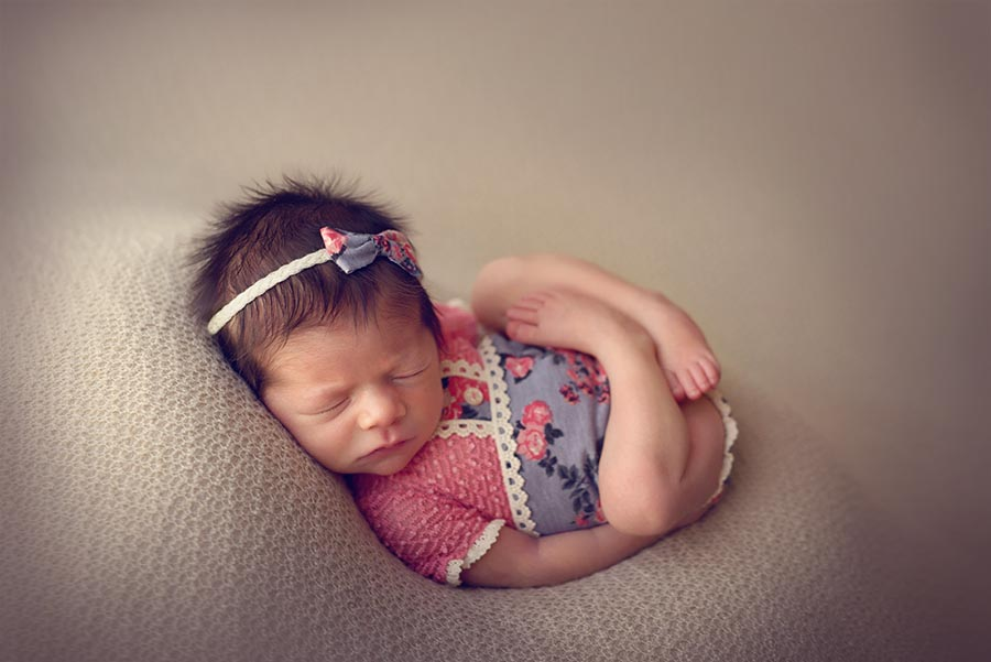Baby girl photographed in a pink and blue floral romper from Adorable props