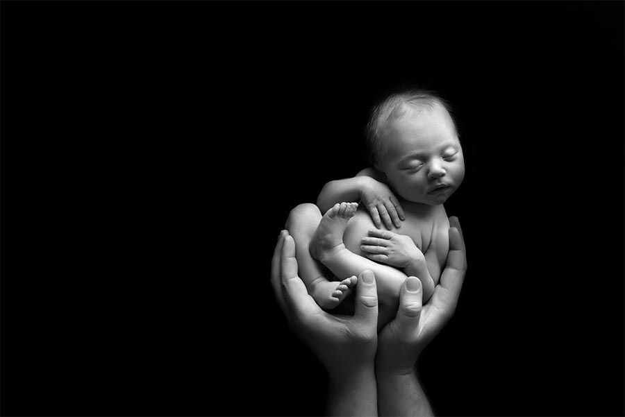 Black and White image of 8 day old baby girl cradled in daddies hands