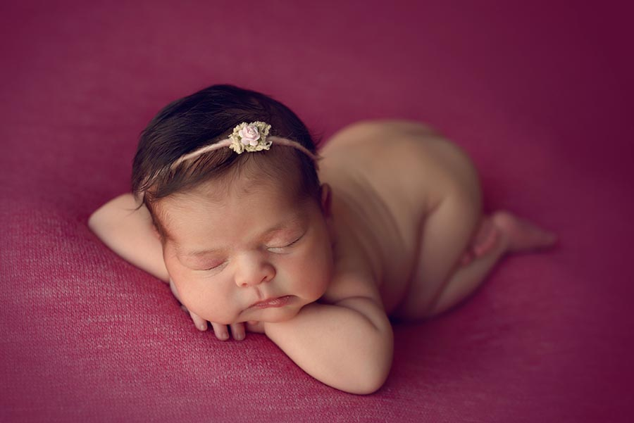 Baby girl on posed with chin on hands on bright pink wearing a delicate tie back from Princess and Pea Prop Shop.