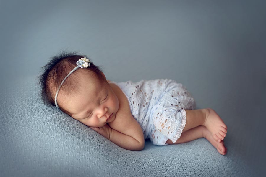 Baby Girl photographed on light blue with a blue romper and tieback