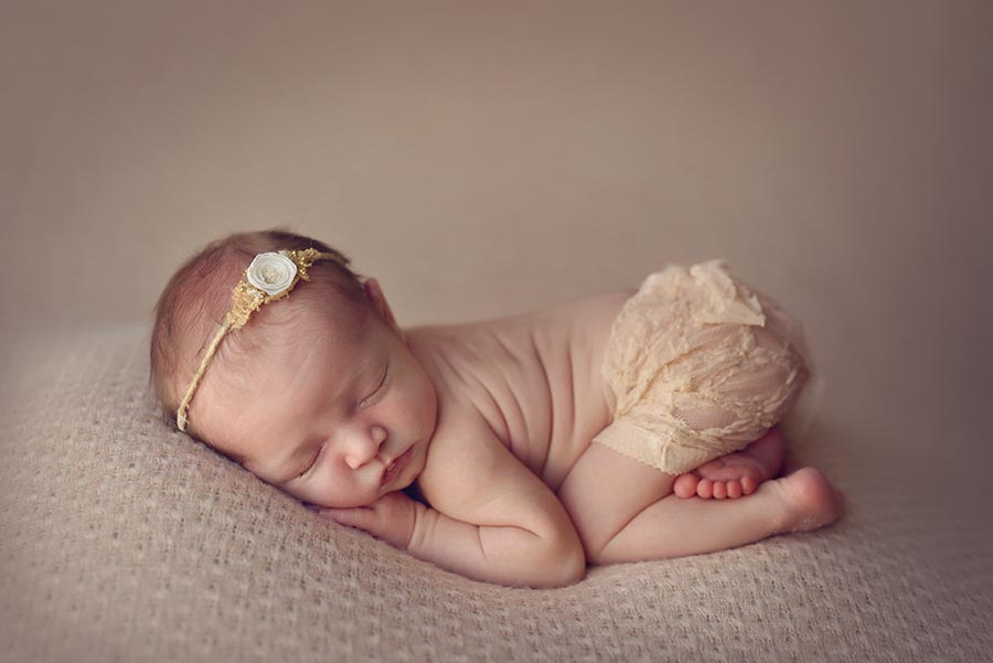 Baby girl wearing gold lace skirt in tushie up pose on a background from AR Backdrops