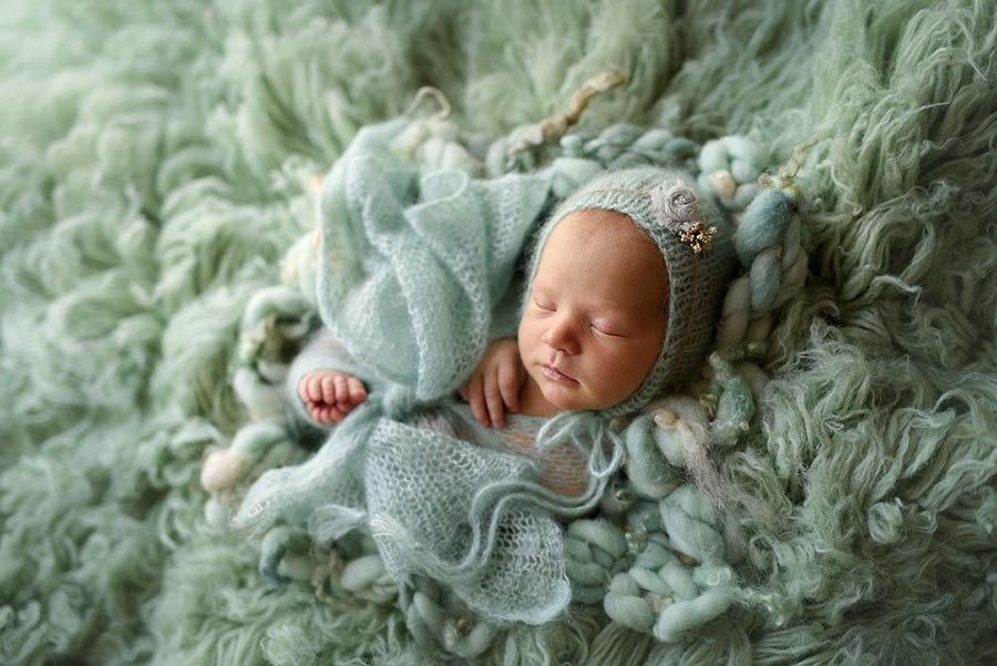 Infant baby girl photographed in mint on a lush thick flokati from Luneberry Designs and swaddled in a mint knit wrap