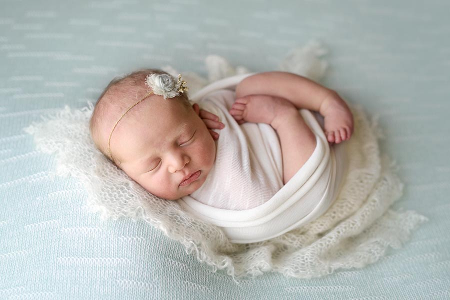 Baby girl photographed on mint in a white wrapped in womb pose in Colorado.