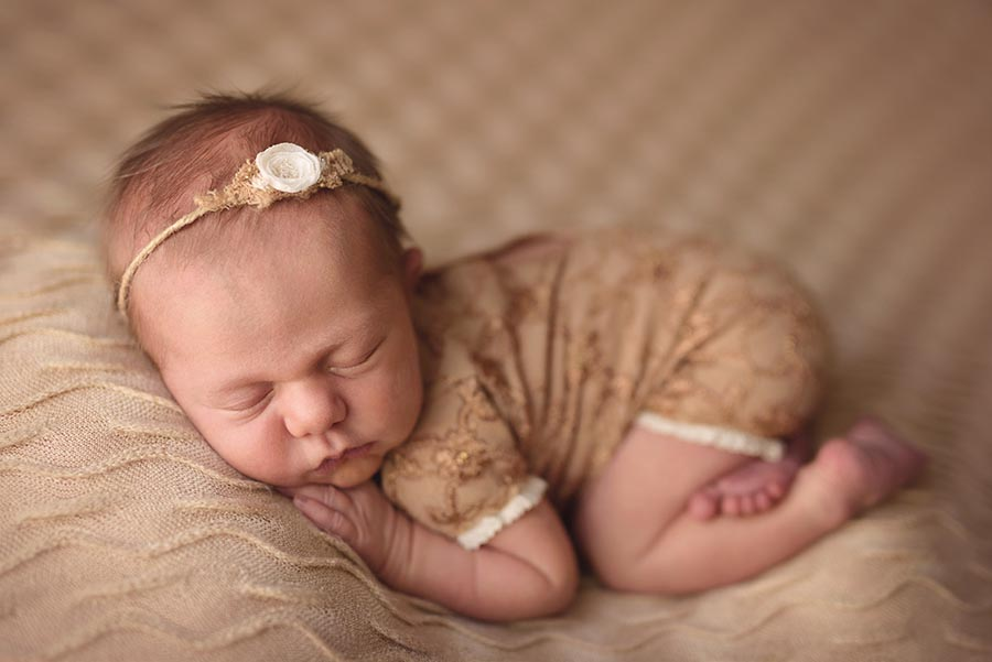 Baby girl photographed in neutral gold gold colors in tushie up pose on a textured background from AR Backdrops and romper from Adorable props