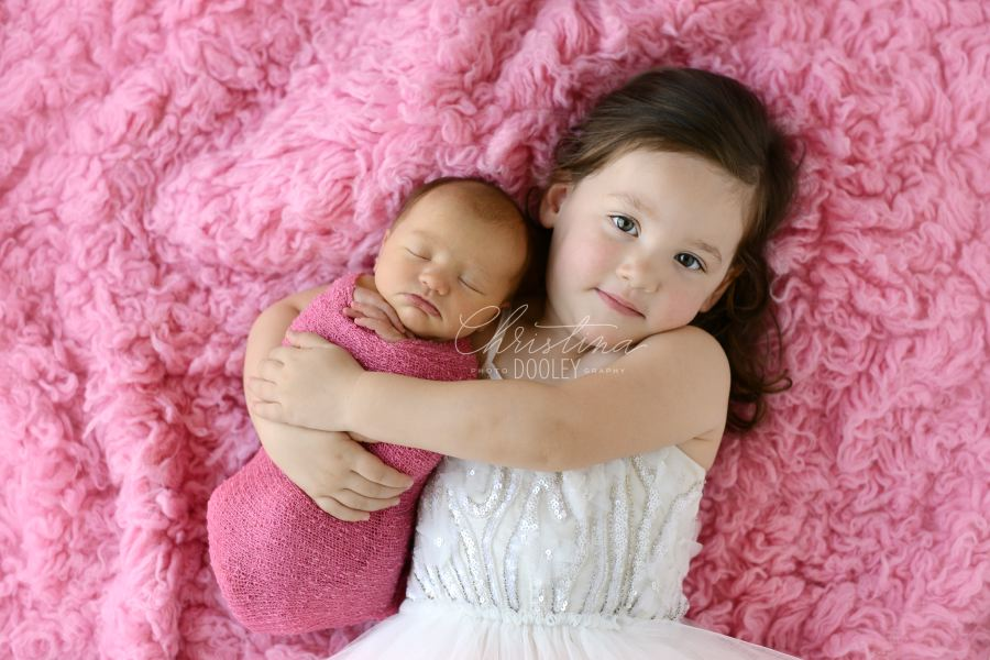newborn baby girl with big sister on pink
