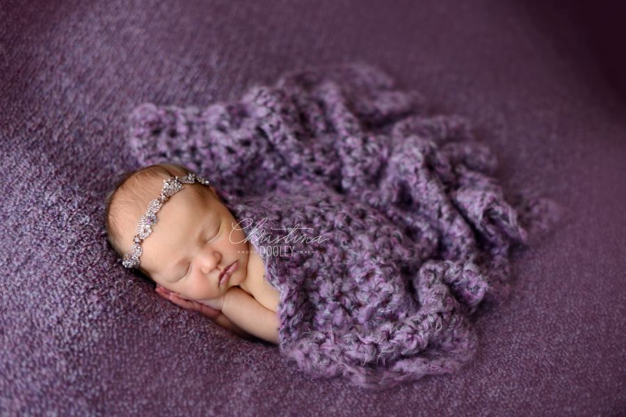 Newborn girl cuddled in a purple crochet blanket and hands delicately placed under her cheek.