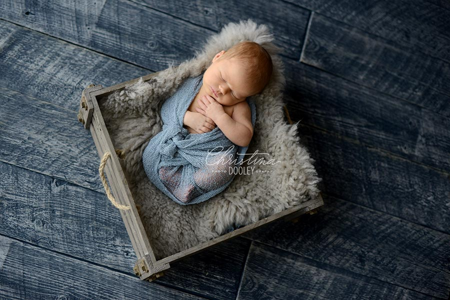 Newborn baby swaddled in blue in a gray crate.
