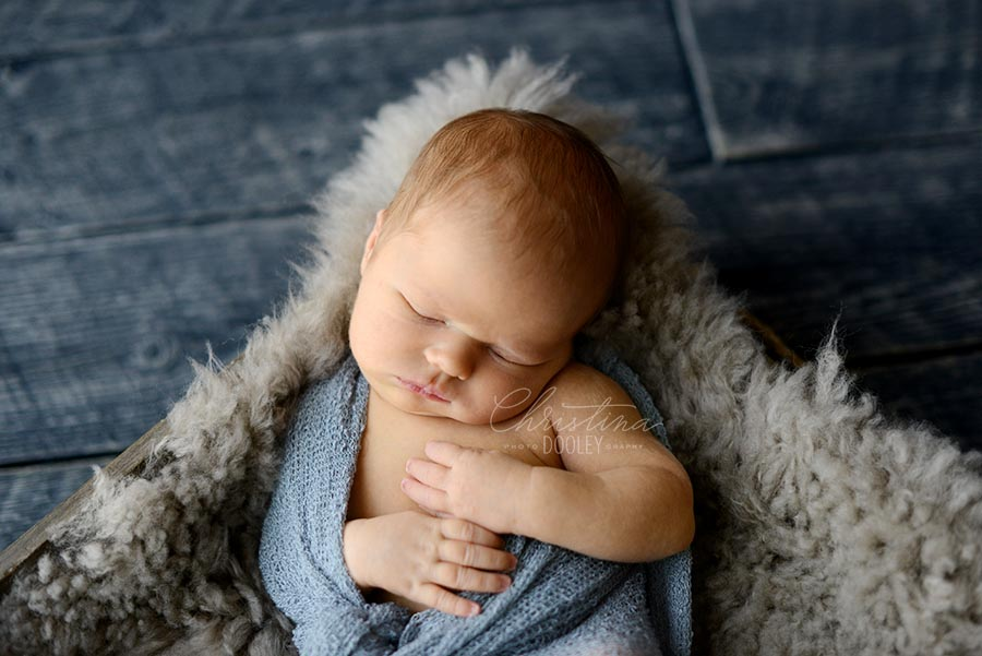 Close up photo of baby boy sleeping on gray.