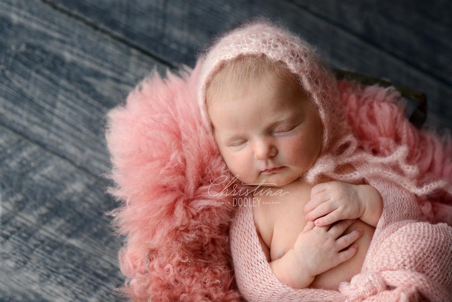 Close Up portrait of newborn girl wearing a knit pink hat on pink fur