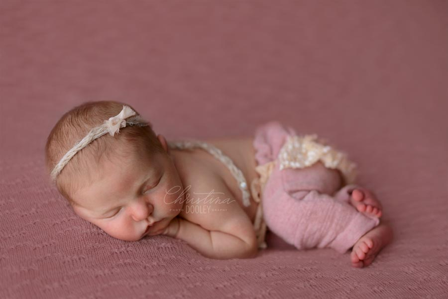 Baby girl sleeping for her newborn photos on pink with pink ruffled bloomer pants and headband from Darling Baby Props