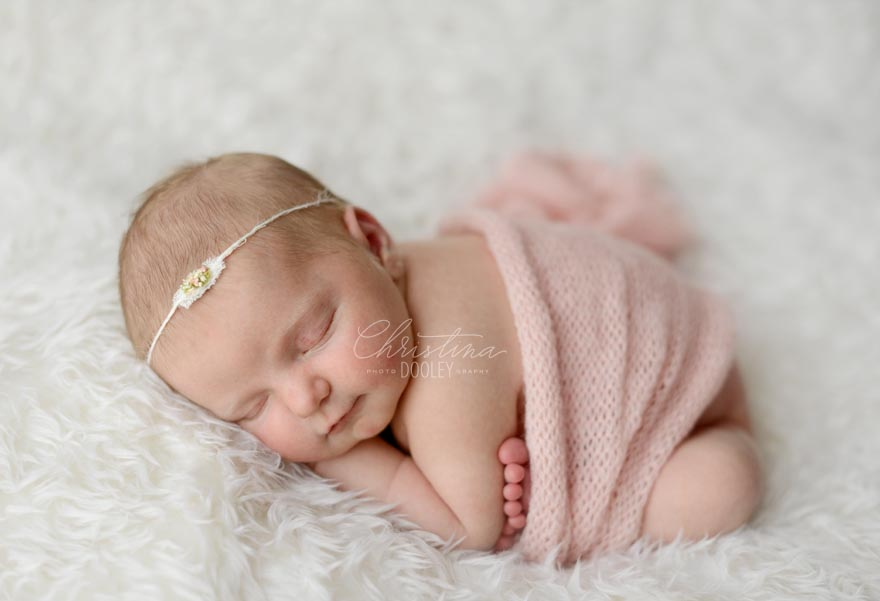 Baby Girls swaddled in pink in the newborn frog pose on white fur