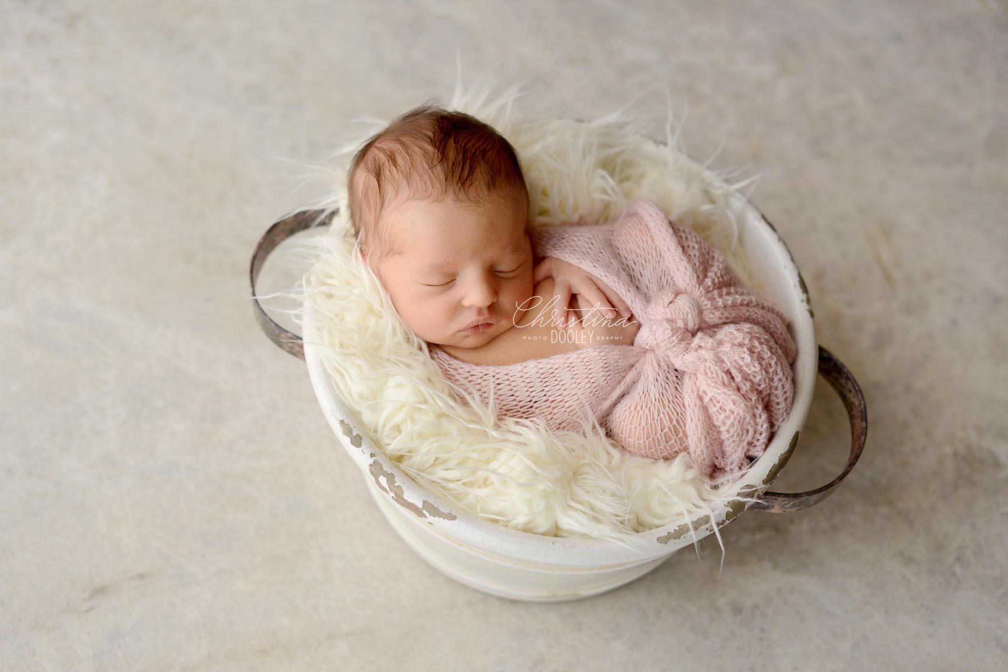 Newborn girl in white bucket on white marble