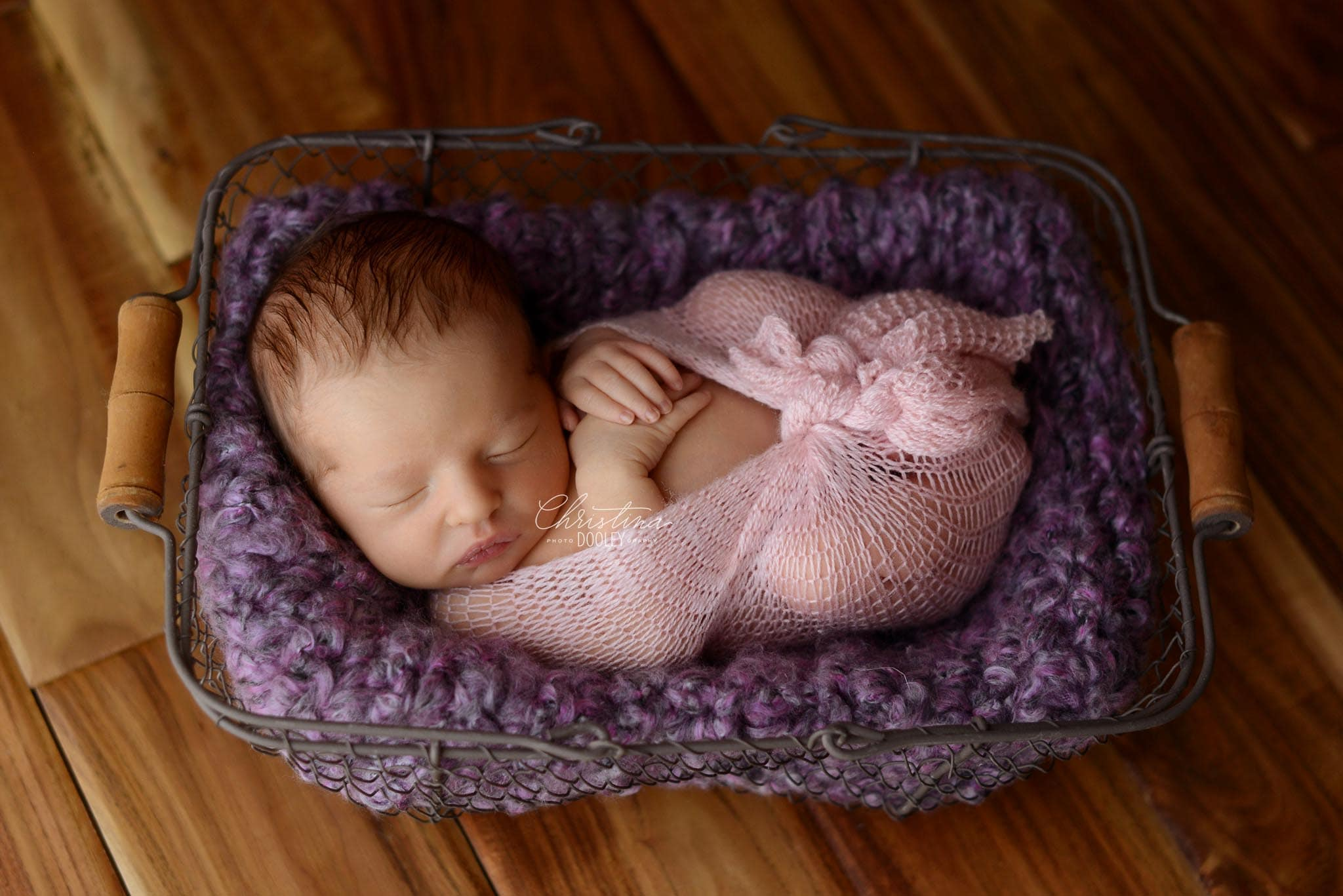 Black and White photo of baby girl in a wire basket