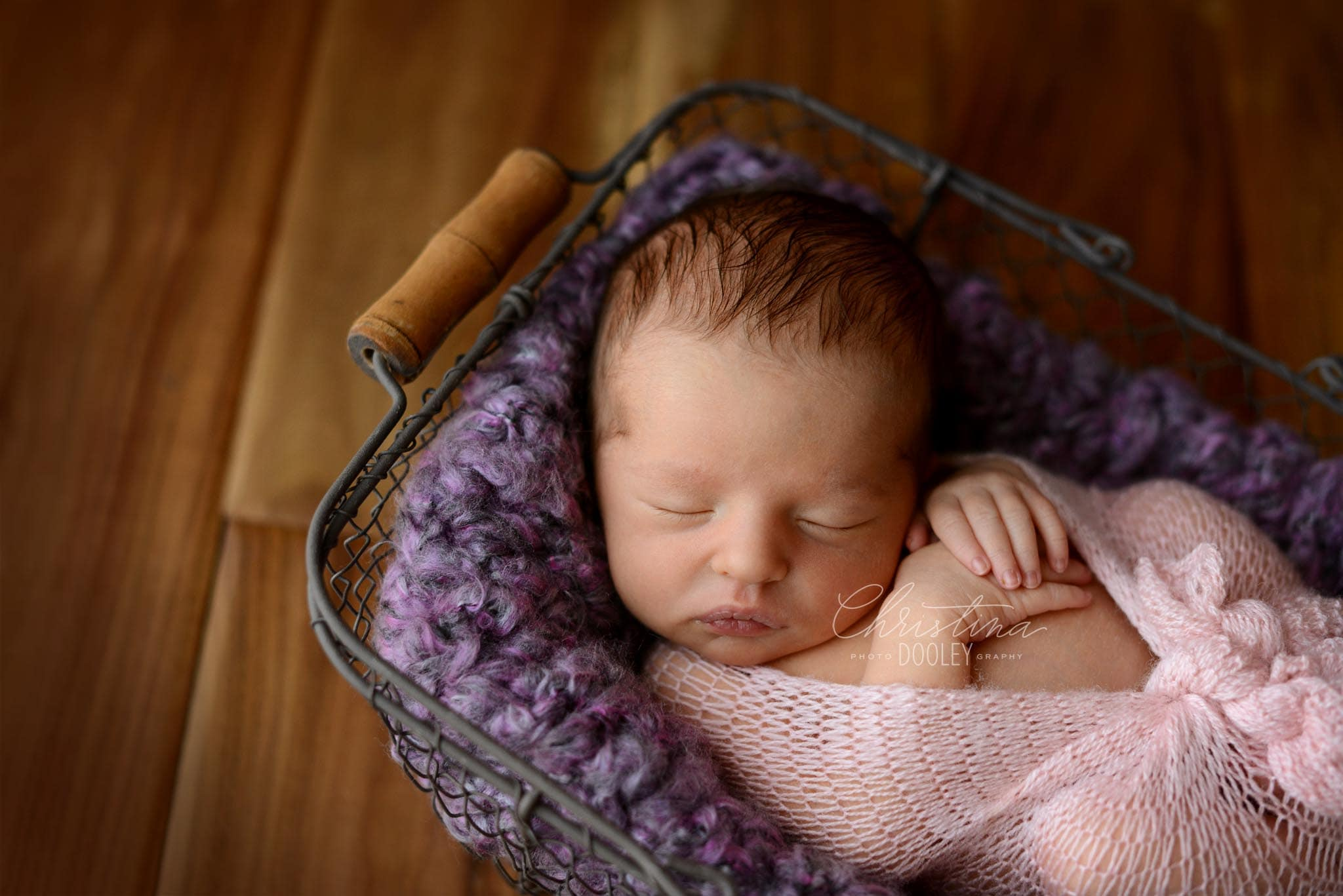 Baby girl wrapped in pink cuddled in a knit purple blanket and placed in a wire basket from JD Vintage Props