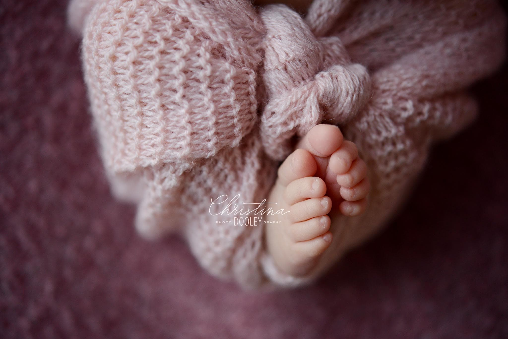 Newborn feet peeking out from knit pink wrap
