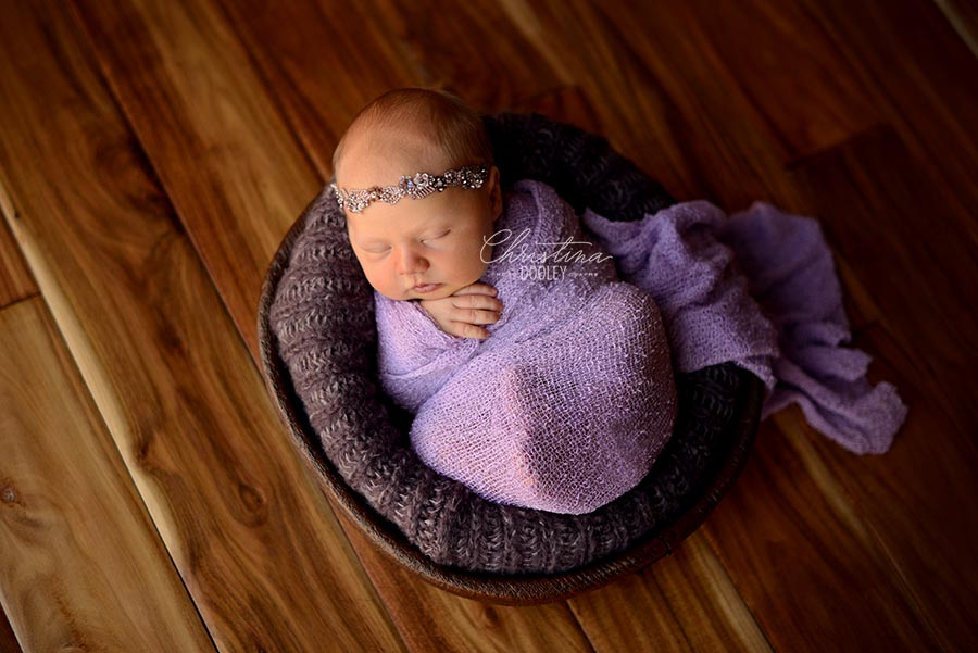 Newborn girl wrapped in purple in a wood bowl from JD Vintage Props