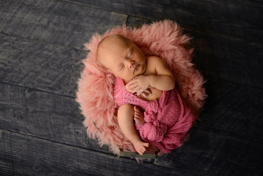 Newborn posed in a bowl wrapped in pink laying on pink fur on a gray floor