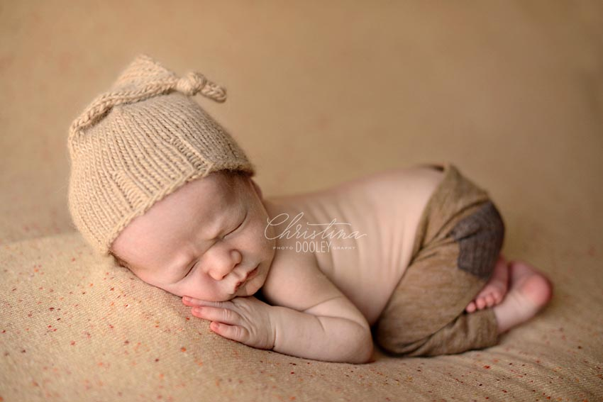 Newborn baby boy with brown knit sleep hat and brown pants