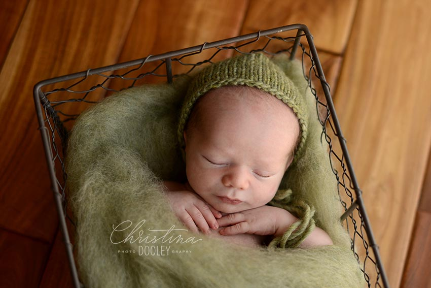 Newborn boy in metal basket from Jd Vintage Props and green hat and fluff from Oh So Fleeting