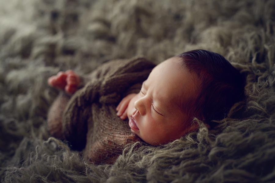 Newborn boy posed on green flokati from JD Vintage Props with beautiful dramatic light.