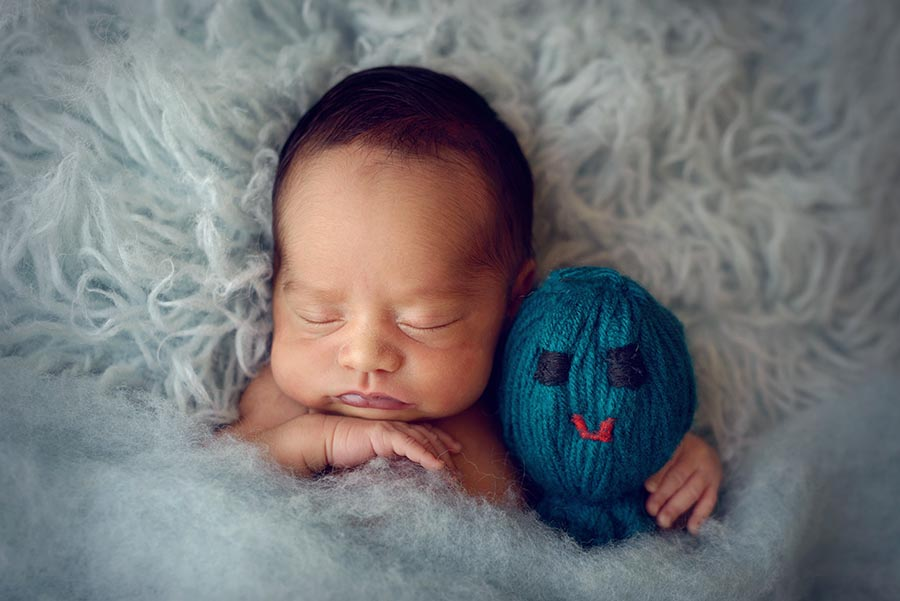 Baby all tucked in on light blue flokati and little stuffy