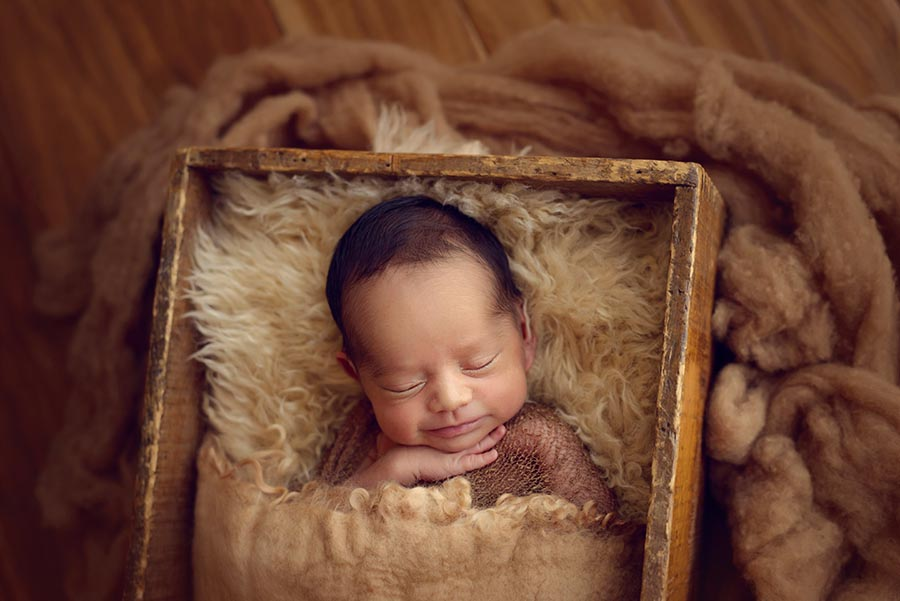 Baby photo smiling while sleeping and posed in a vintage box on wood floors in Denver, Colorado at Christina Dooley Photography's studio